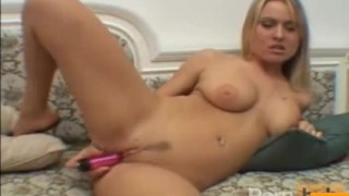 Busty blonde chick masturbates on the couch