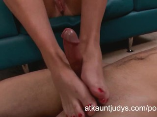 Cougar Bianca Breeze gives a footjob to a young man.