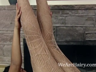 Yonique stripping for hairy fun by the fireplace