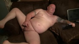 chubby tattooed guy with pierced cock jacks off to porn