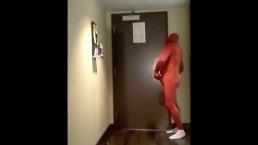 red morphsuit jerking off at hotel room door