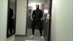 skeleton faced white socked black morphman in front of hotel room