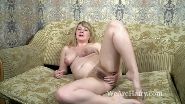 Hairy blondes naked Evlalia strips naked and masturbates on her sofa
