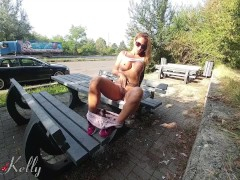 Tattooed busty blonde masturbates outdoor on a crowded national road