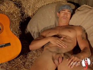 Muscle guitarist plays with the hay...