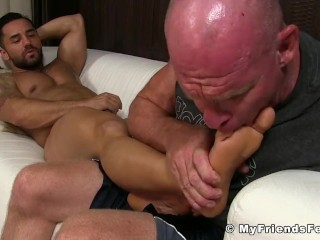 Tattooed muscular hunk masturbating while his feets get licked