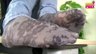 Teen feet in socks with white nail polish