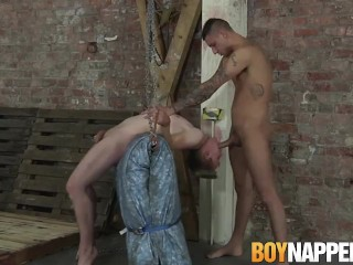 Restrained submissive twink gets fed cock by inked stud
