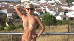 Rubia desnuda está caminando en la ciudad española.