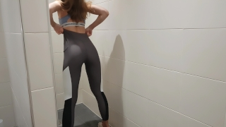 Fit girl masturbates in a gym bathroom