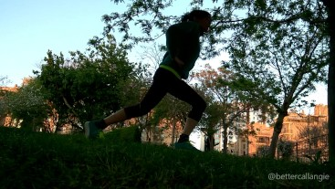 Doing lunges in a public park at sunset, voyeur clip from the grass