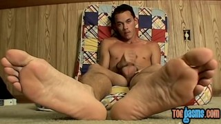 Skinny dude rubs his cock and feet at the same time solo