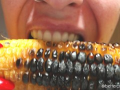 I bite and chew a delicious roasted corncob, a close-up of my sharp teeth