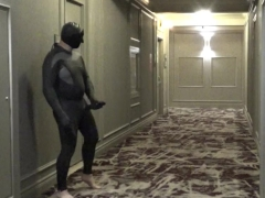 barefoot masked wetsuited guy in hotel hall with cock extension