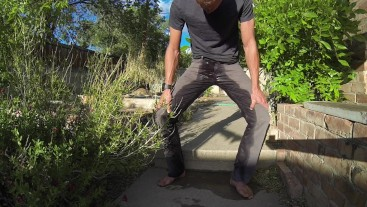 Pissing grey jeans in a huge flood outdoors