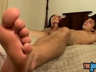 Cute young man jerks off with his perfect feet in the front