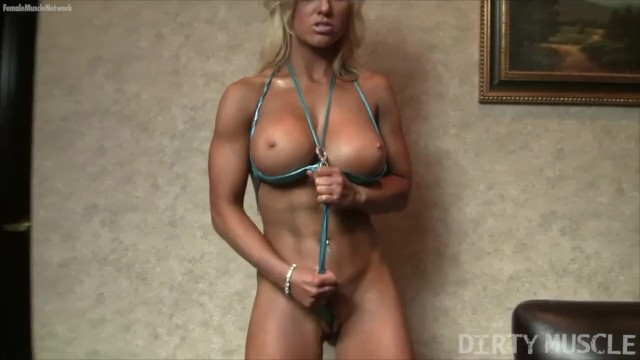 In a string bikini Blonde muscle barbie poses in a string bikini and gets wet