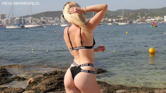 Young Blonde In Black Bikini Doing Photo Shoot Outdoors On The Beach
