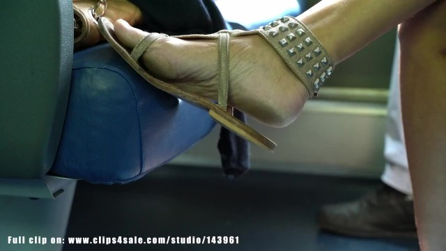 Detailed description of the pandas thumb Candid woman dirty feet and sandals, detailed and sexy, on train bench