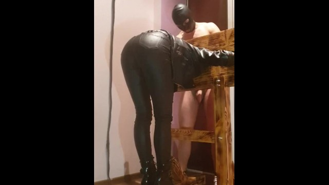 Erotic images of the pillory - Hard spanking whore in leather jacket pants and boots in pillory stocks
