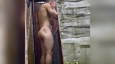 hot guy washes in the shower in nature