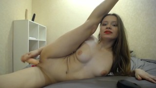 Cam girl with red lips fucking herself by dildo with legs behind head