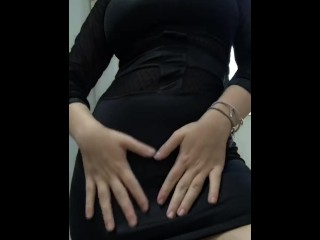 Latina wearing a tight black dress and showing her thong