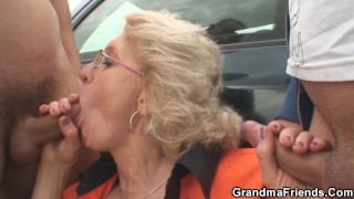 Blonde old woman pleases two strangers in the fields