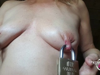 Nippleringlover inserting a big padlock through stretched pierced...