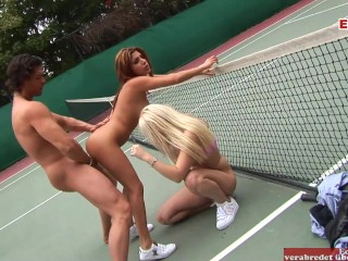 Threesome on a tennis court slim brunette and...