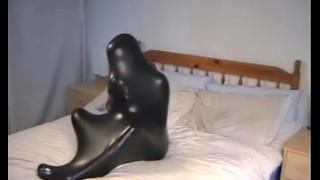 Cute girl in black latex catsuit with mask makes self bondage in rubber vacuum sleepbag - part 2