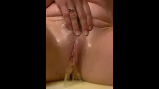 Naked MILF all wet in the shower, she pisses all over the shower chair & plays with her soaked pussy