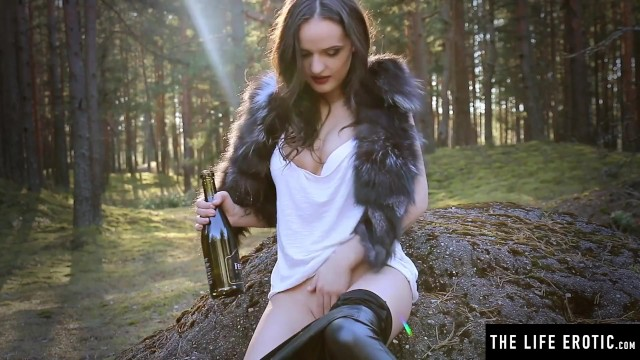Horny brunette fucks her pussy with a wine bottle in the woods 6