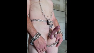 Male slave in chain bondage, CBT, and nipple clamps.